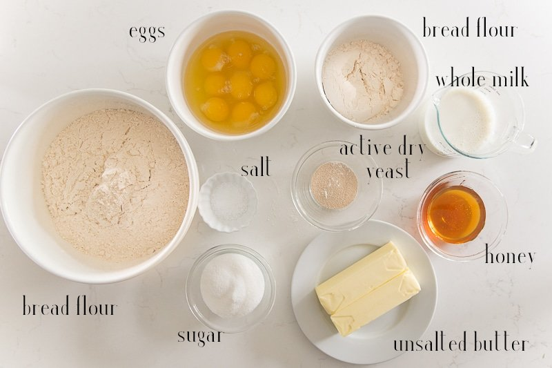 Ingredients to make Brioche Bread labeled in black text: eggs, bread flour, whole milk, active dry yeast, honey, unsalted butter, sugar, salt and a larger quantity of bread flour.