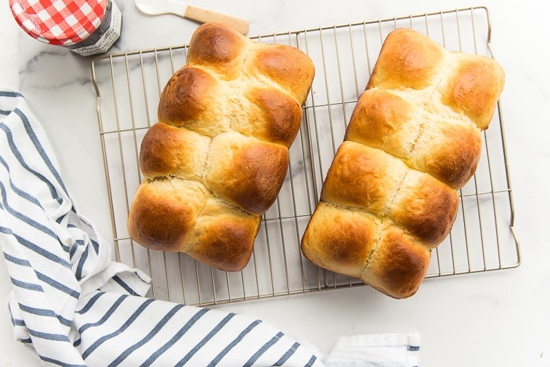 Two loaves of baked brioche bread on a silver wire rack. Blue and white striped napkin furled next to the rack. Jam jar with a red and white checkered lid