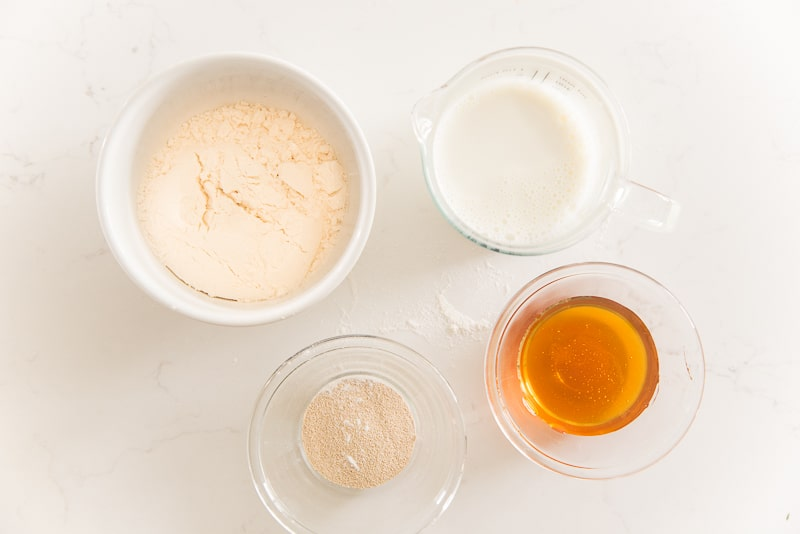 The starter ingredients on a white surface: bread flour, milk, honey, and yeast.