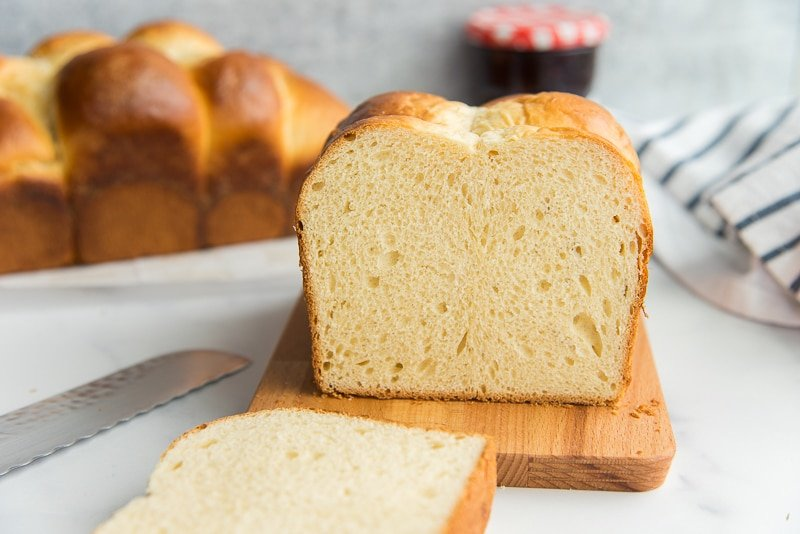 Horizontal image of a sliced loaf of brioche bread on a wood board