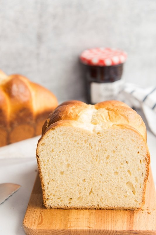 Cut loaf of Brioche bread on a wood board. Second loaf in background next to a red and white capped jelly jar