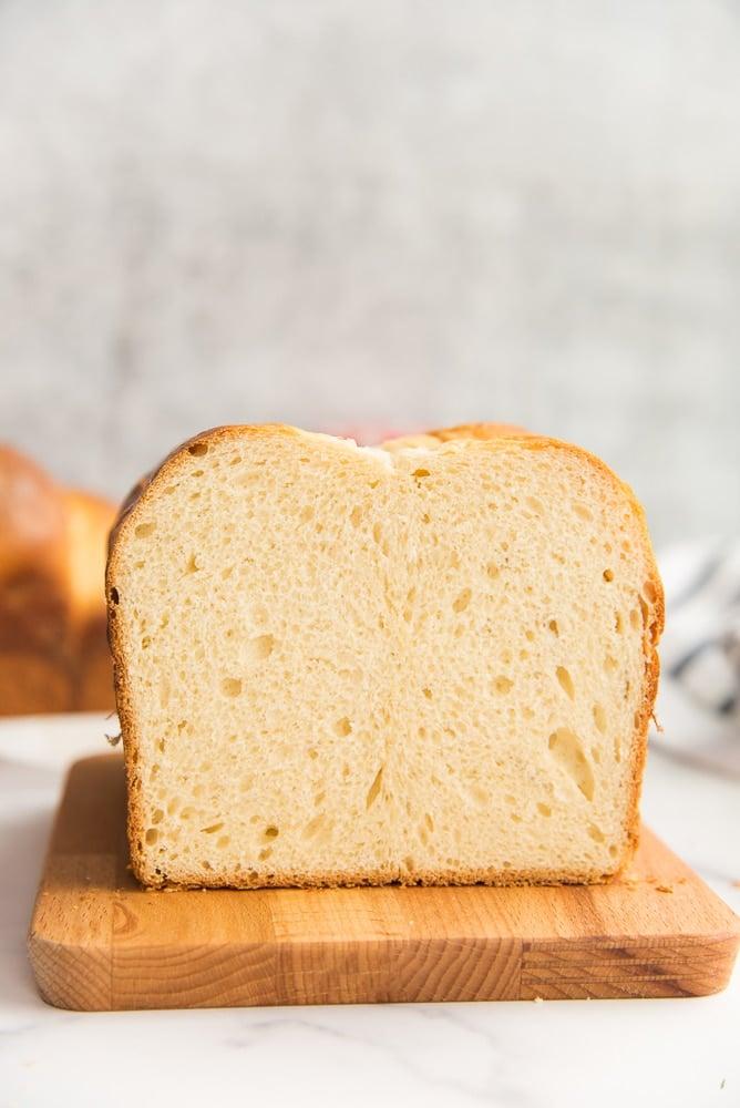 Lead image of a cut loaf of Brioche Bread on a wooden board.