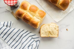 Preview image of Brioche Bread with the heel pulled off to show interior texture of bread. White and blue kitchen towel bottom left. Red and white checkered capped jam jar top left. Corner of another loaf of brioche in top right.