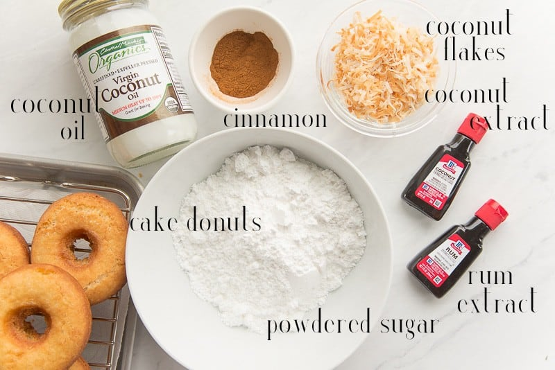 Ingredients to make Coquito Cake Donuts: coconut oil, cinnamon, coconut flakes, coconut extract, rum extract, powdered sugar, and cake donuts