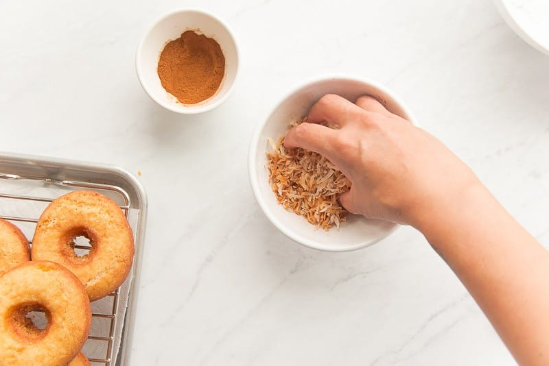 A hand tosses cinnamon into a bowl of toasted coconut flakes