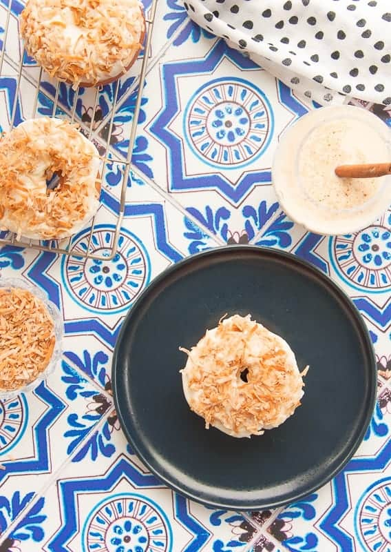 Overhead portrait of a coquito cake donut on a blue plate next to a rack of coquito donuts