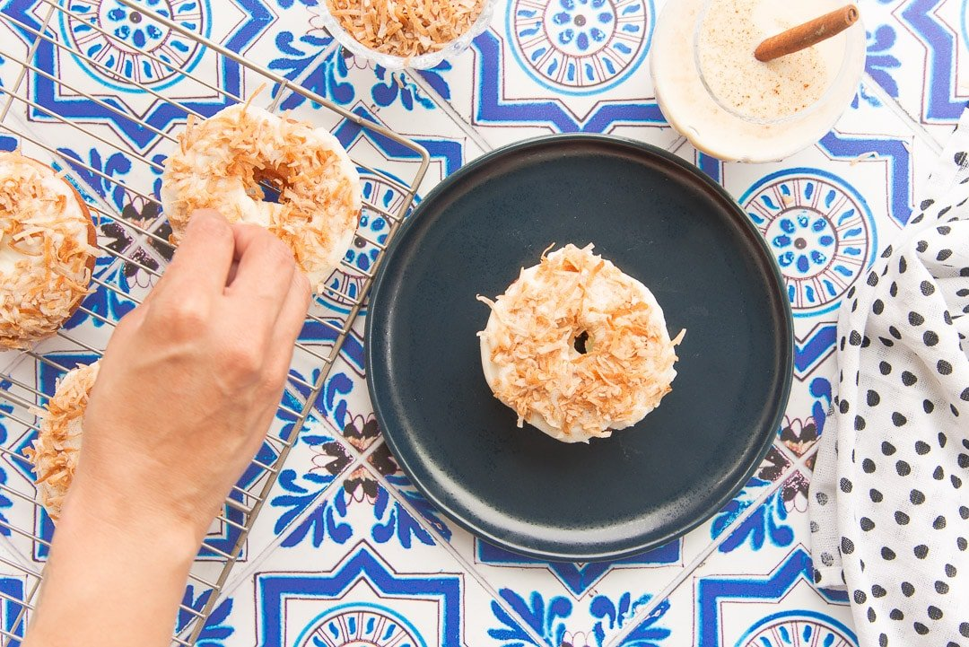 blue plate with Coquito Cake Donut on it coquito in a glass garnished with a cinnamon stick blue mosaic tile background