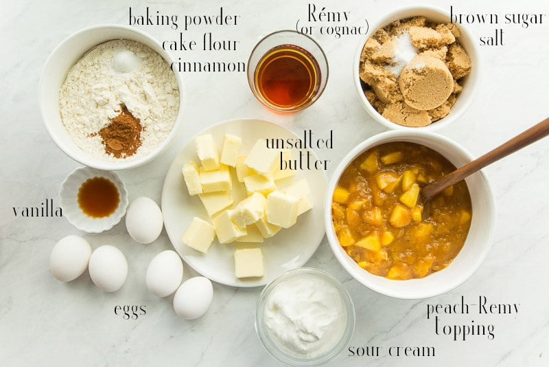 The ingredients needed for the recipe: baking powder, cake flour, cinnamon, Remy, brown sugar, salt, unsalted butter, peach-Remy topping, sour cream, eggs, and vanilla.