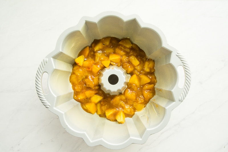 The peach topping is in the bottom of a metal bundt pan.