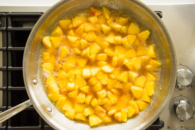 The cognac is added to the pan of simmering peaches.