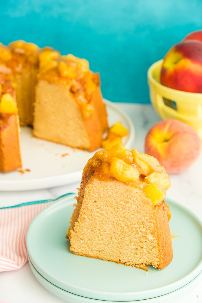 Lead image of a slice of Remy Pound Cake with Peach Topping on a green plate in front of a teal background.