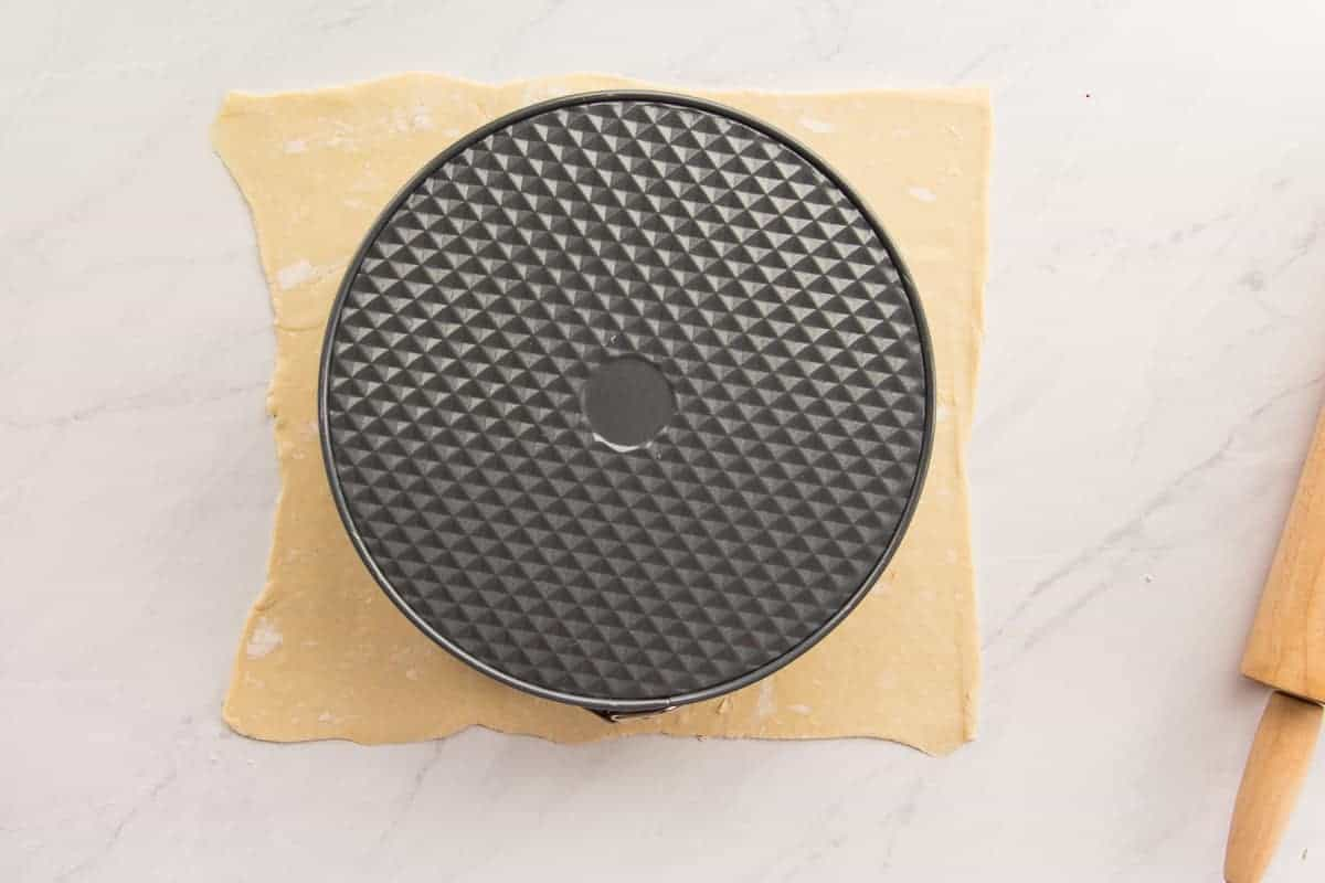 The cheesecake pan inverted onto a sheet of pastry to use a template to cut the wedges for garnish.