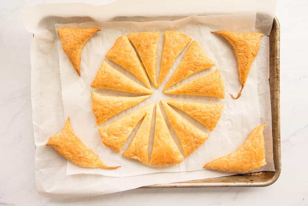 The puff pastry circle is baked after being cut into wedges on a parchment lined sheet pan.