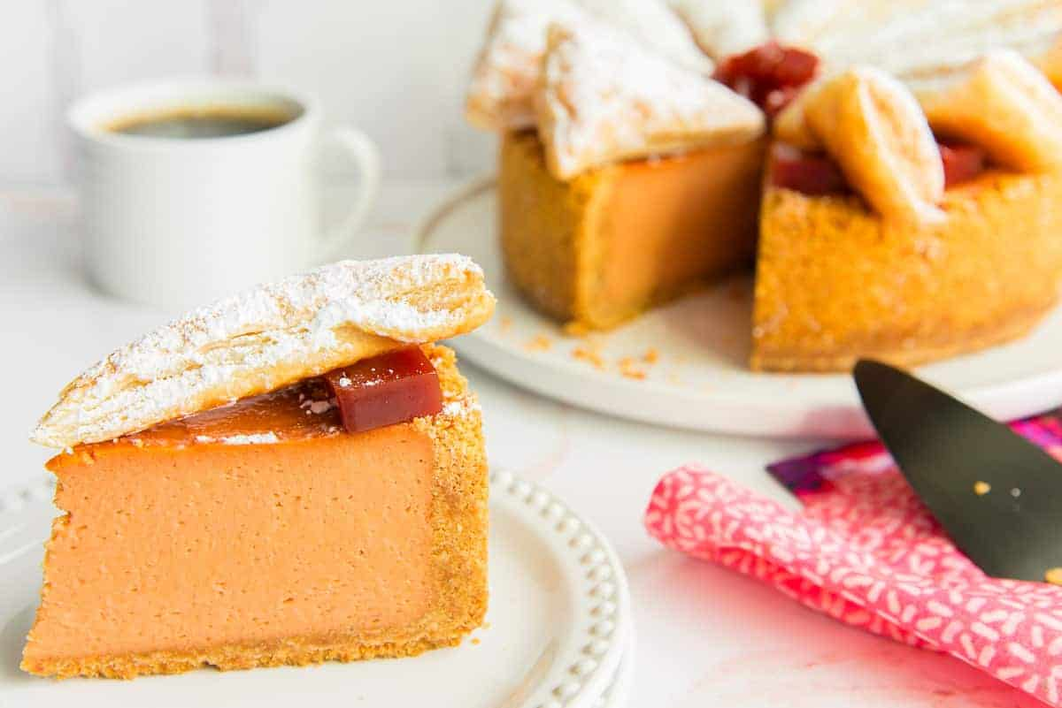 Horizontal image of a slice of Pastelillo de Guayaba Cheesecake on a white plate in front of a white mug of coffee and the rest of the cheesecake.