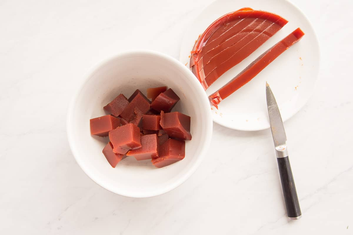 Guava paste is cut into chunks and added to a white mixing bowl from a white plate.