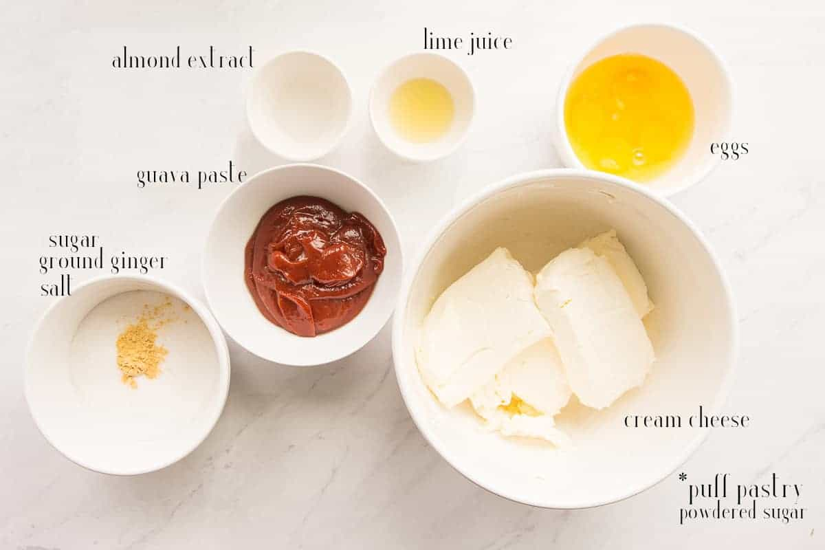 Ingredients needed to make Pastelillo de Guayaba Cheesecake: almond extract, lime juice, eggs, cream cheese, guava paste, sugar, ground ginger, salt. Not pictured: puff pastry sheet and powdered sugar.