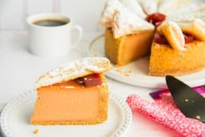 Preview image: A slice of Pastelillo de Guayaba Cheesecake on a white plate in front of a mug of coffee and the rest of the cheesecake.