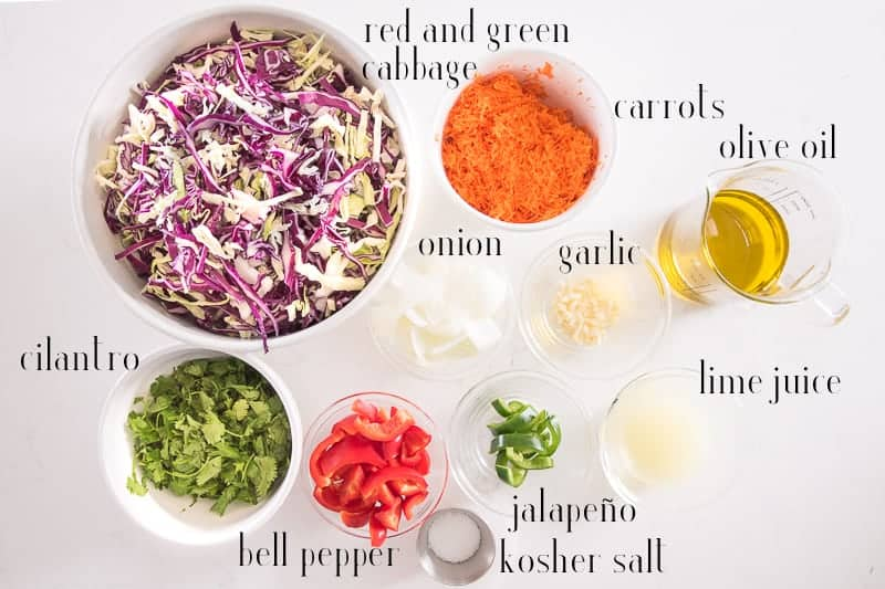 Ingredients needed to make Peruvian Inspired Coleslaw are pictured on a white surface: red and green cabbage, carrots, onion, garlic, olive oil, lime juice, jalapeno, kosher salt, bell pepper, cilantro.