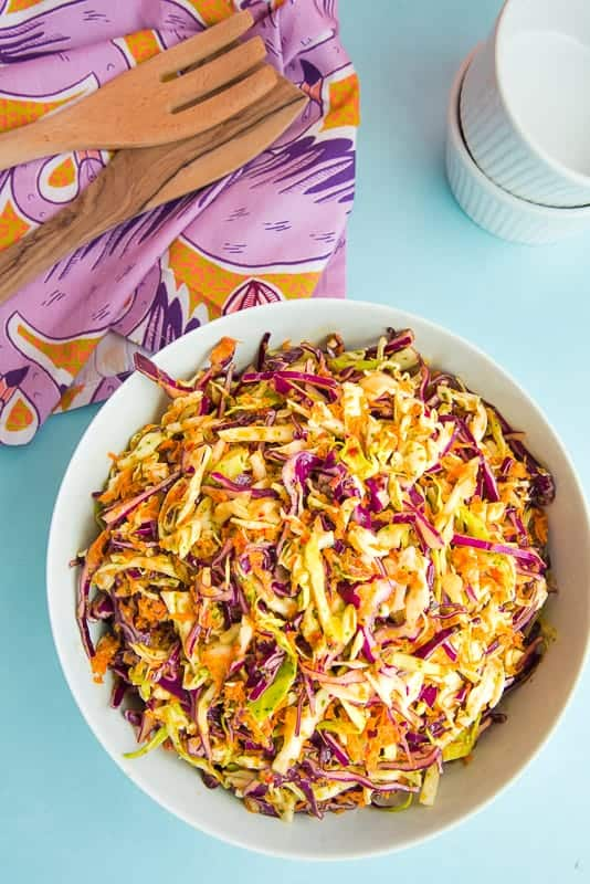 Overhead image: white serving bowl filled with Peruvian Inspired Coleslaw on a light blue surface. Top right corner: purple kitchen towel with two wooden utensils on top. Top right image: two stacked ramekins.