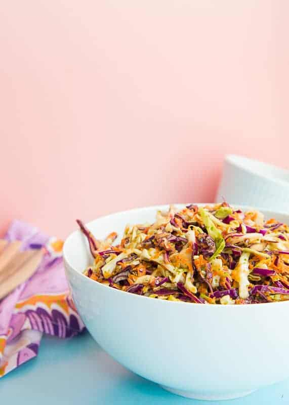 Portrait image: white ceramic bowl filled with Peruvian Inspired Coleslaw. Left background: purple kitchen towel with wooden utensils on top. Right background: white ceramic ramekin.