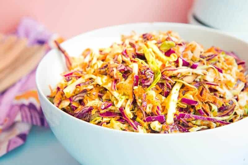 Horizontal image white bowl red and green cabbage coleslaw pink background