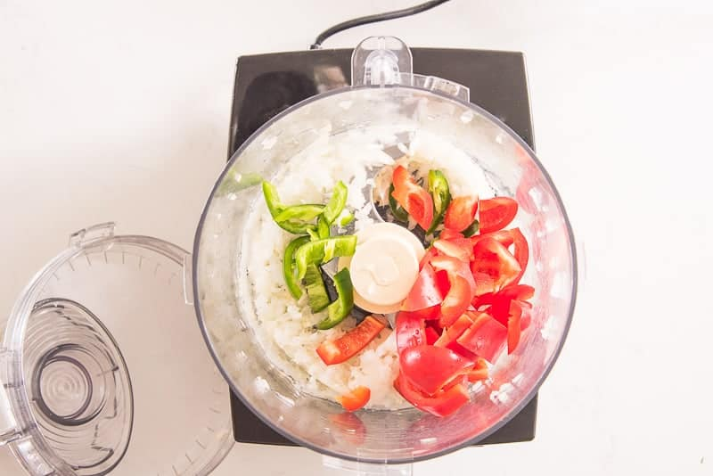 Chopped red bell pepper and jalapenos are added to a food processor with chopped onions and garlic.