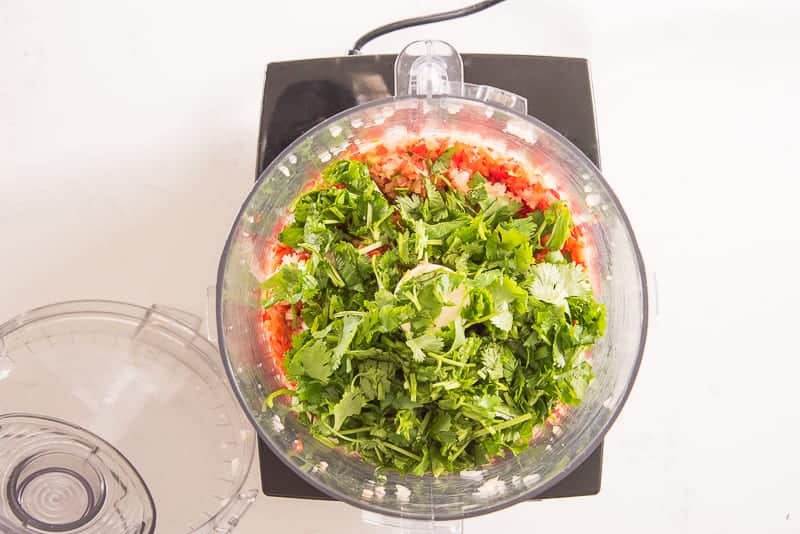 Cilantro is added to a food processor with chopped vegetables in it.