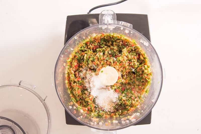 Salt and lime juice is added to a food processor with chopped vegetables in it