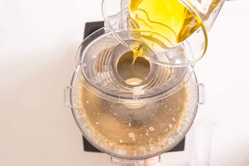 Olive oil is poured from a clear glass measuring cup into the Chute of a running food processor