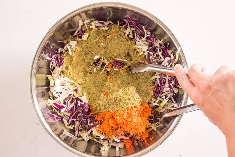 A hand uses silver tongs to toss green dressing into red and green shredded cabbage and shredded carrots in a silver mixing bowl.