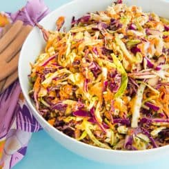 Horizontal image: white bowl with red and green cabbage coleslaw inside. Left of bowl: a purple kitchen towel with two wooden utensils on top.
