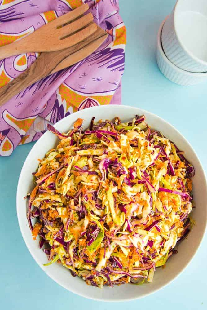 Lead image: a white bowl of Peruvian Inspired Coleslaw on a light blue surface. Top left of image: purple kitchen towel with two wooden utensils on top of it. Top right of image: two stacked white ramekins.