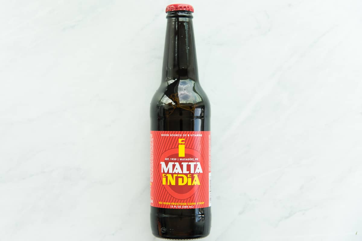 A bottle of Malta India on a white marble surface