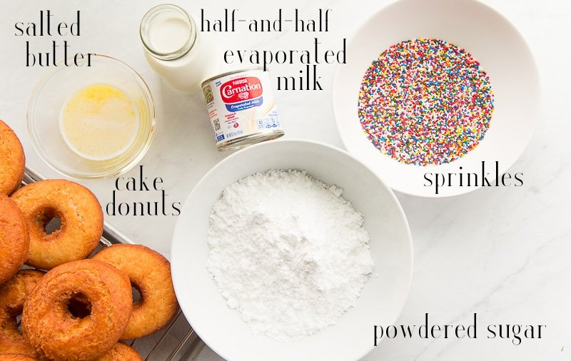 Ingredients to make Tres Leches Cake Donuts on a white surface: melted salted butter, half and half, evaporated milk, sprinkles, powdered sugar, cake donuts.