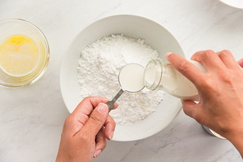 Half and half is added to a white bowl filled with powdered sugar.