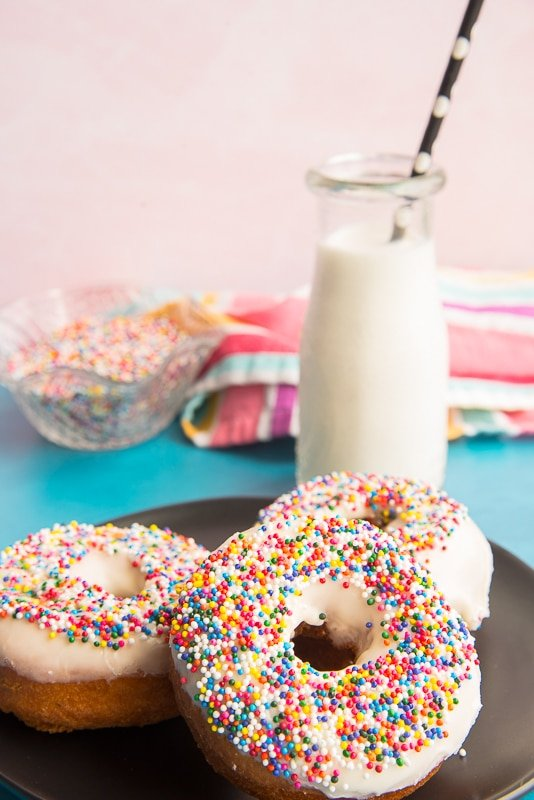 Portrait image of black plate with three sprinkle topped Tres Leches Cake Donuts in foreground. A small bottle of milk in left background.