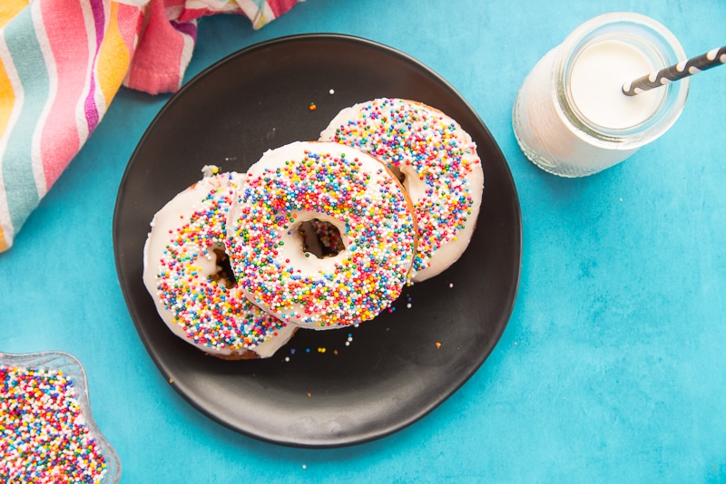 Three Tres Leches Cake Donuts on a black plate to the left of a small bottle of milk with a black and white straw in it. A multicolored towel is furled in top left corner.
