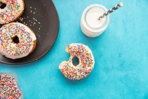 A Tres Leches Cake Donut with rainbow sprinkles a bite removed from the donut on a blue surface next to a black plate with 2 donuts on it. A bottle of milk at top center with a black and white straw in it.