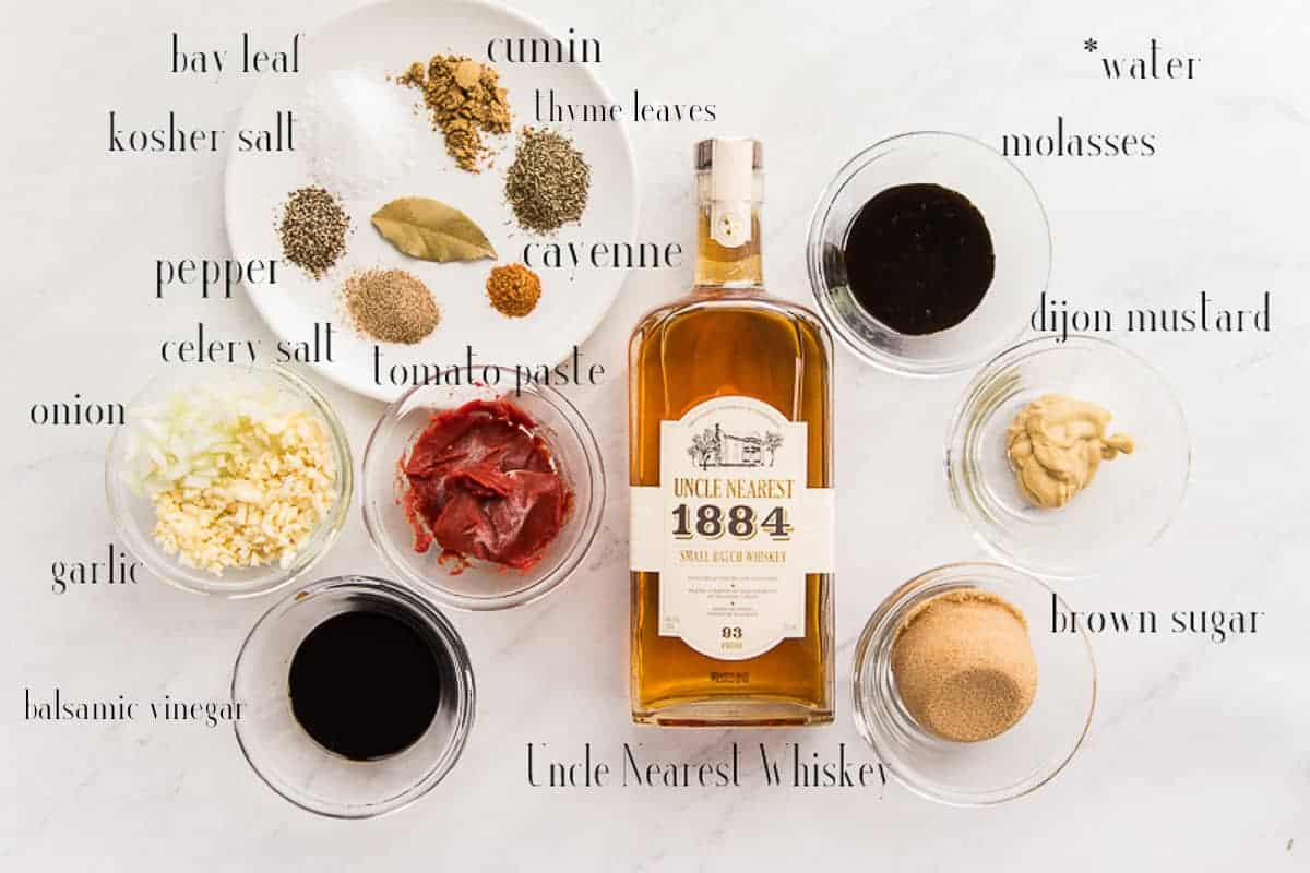 Ingredients needed to make Uncle Nearest Whiskey BBQ Sauce arranged on a white surface: bay leaf, kosher salt, pepper, celery salt, cayenne pepper, oregano, cumin, molasses, Dijon mustard, brown sugar, Uncle Nearest Whiskey, tomato paste, soy sauce, garlic, and onion.