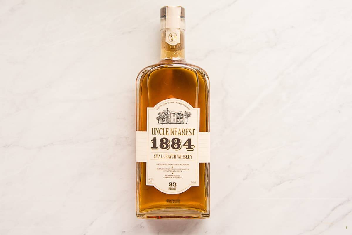 Bottle of Uncle Nearest 1884 small batch whiskey on a marble surface.
