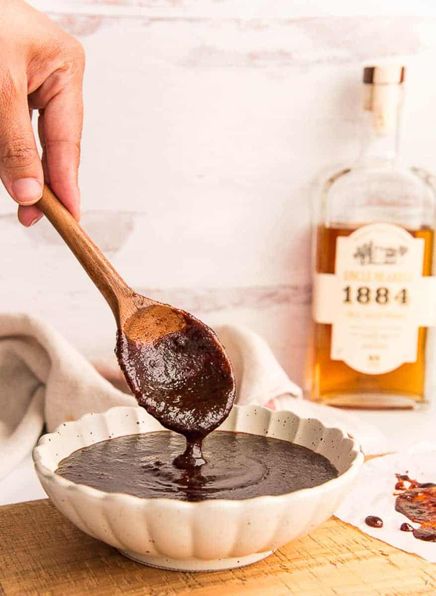 Portrait image: hand lifts a spoonful of Uncle Nearest Whiskey BBQ Sauce from bowl set on a wooden surface.