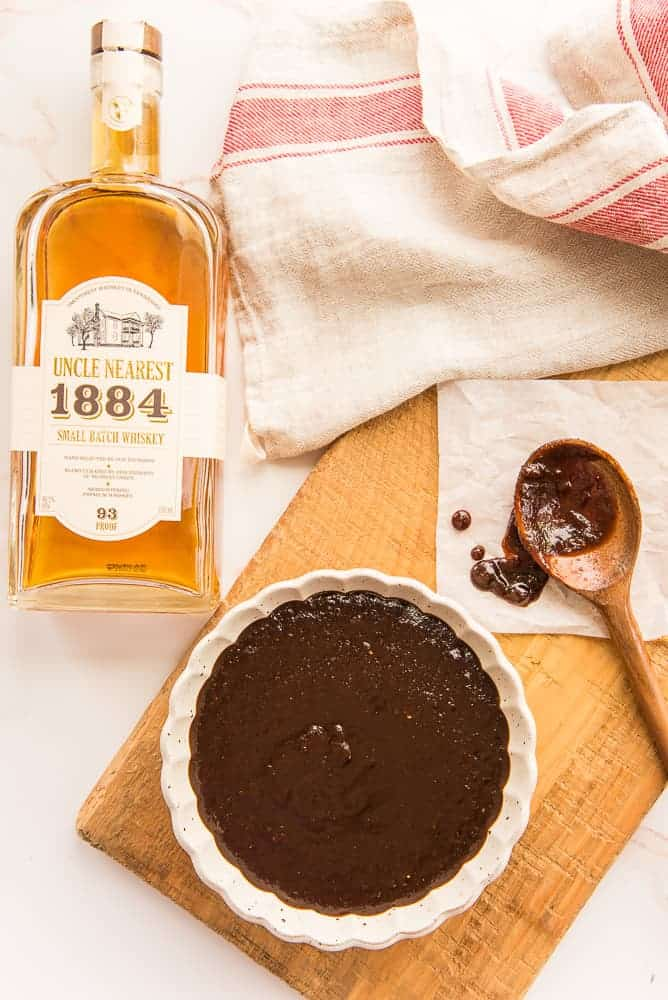 Lead image: bottle of Uncle Nearest Whiskey next to a wooden surface with a beige bowl filled with Uncle Nearest Whiskey BBQ Sauce.