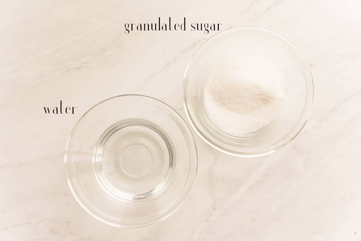 Ingredients needed to make simple syrup: sugar and water in clear glass bowls.