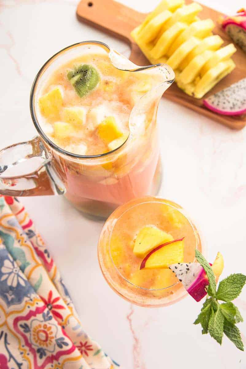 Overhead portrait image of a glass pitcher of Tropical Sangria next to a wine glass of sangria garnished with a wooden skewer of pineapple, mango, and dragonfruit.