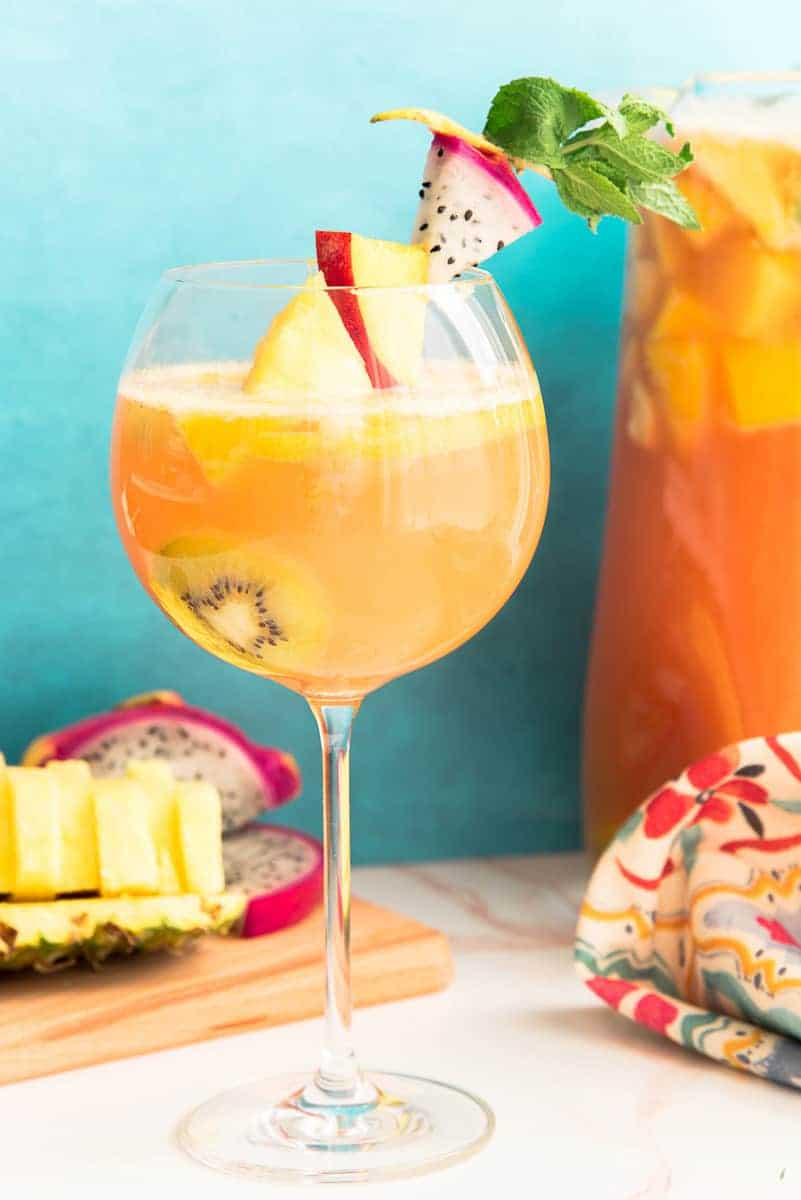portrait image of a wine goblet filled with Tropical Sangria in front of a clear glass pitcher. Bottom left of image a wooden cutting board with a sliced pineapple and dragonfruit on it.