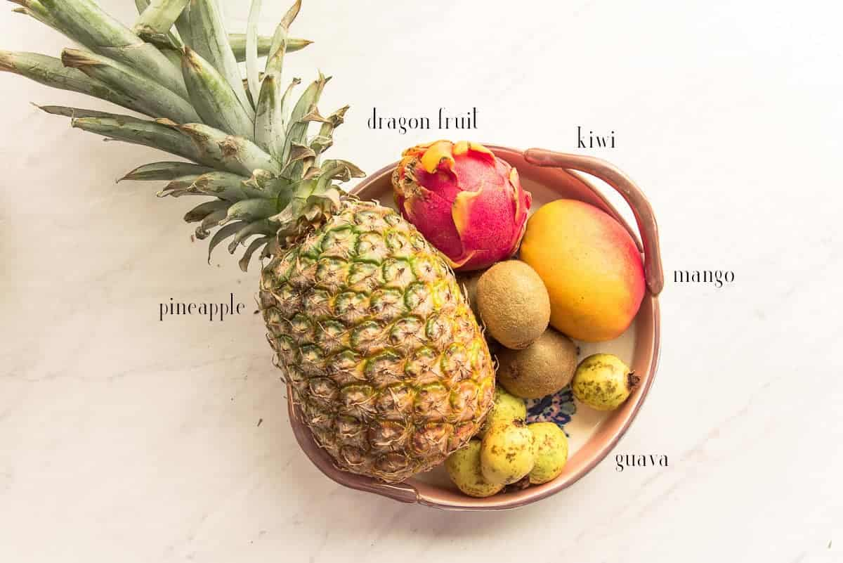 Fruit that will be cut and added to the Tropical Sangria in a ceramic serving tray: pineapple, dragonfruit, kiwi, mango, and Mexican guava