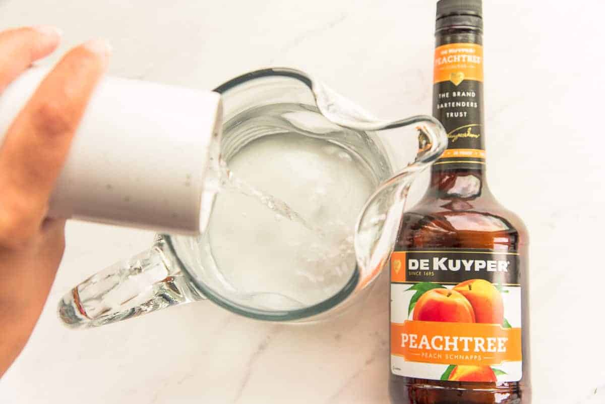 Peach schnapps is poured from a small white pitcher into a glass pitcher of simple syrup