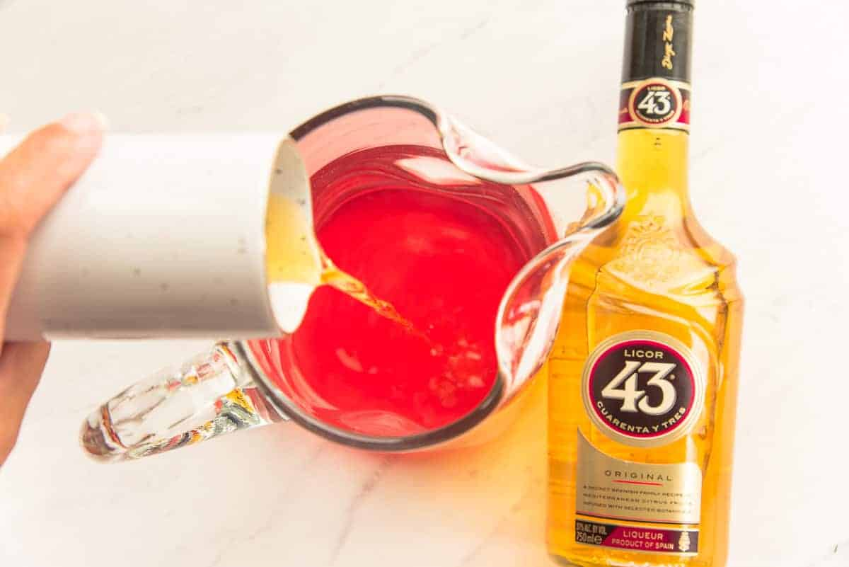 Licor 43 is poured from a small white pitcher into a clear glass pitcher.