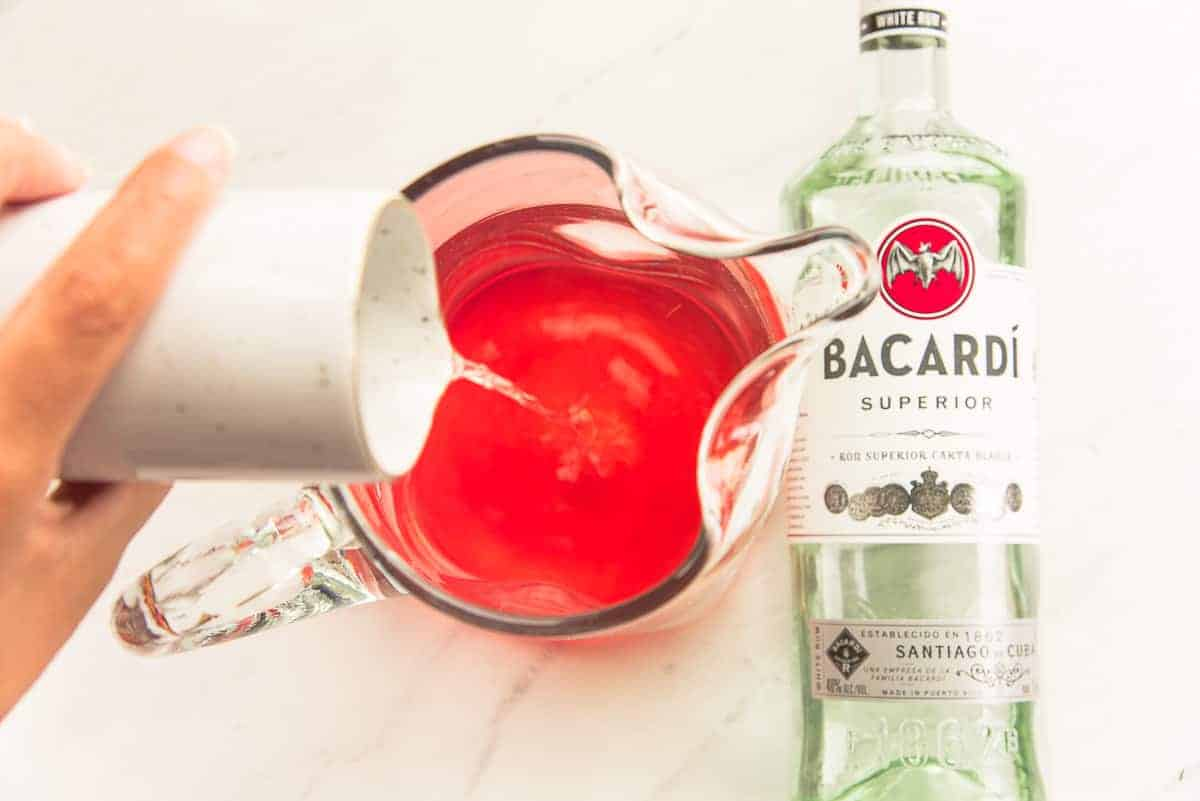 White Bacardi rum is poured into a clear glass pitcher from a small white pitcher.