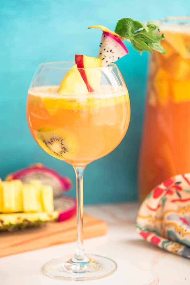 Lead image of Tropical Sangria in front of a blue-green background and a pitcher of sangria.